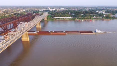 Aerial-of-river-barge-under-three-steel-bridges-over-the-Mississippi-River-with-Memphis-Tennessee-background