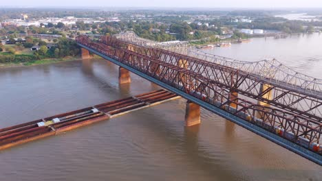 Aerial-of-river-barge-under-three-steel-bridges-over-the-Mississippi-River-with-Memphis-Tennessee-background-2
