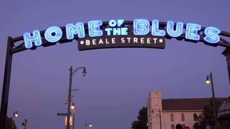 Night-or-dusk-shot-of-the-Beale-Street-Memphis-arch-sign-entertainment-district-with-tourists-arriving