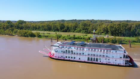 Beautiful-aerial-shot-of-a-paddlewheel-steamboat-luxury-cruise-ship-on-the-Mississippi-River-near-West-Helena-Arkansas