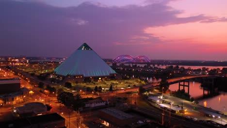 Beautiful-night-aerial-shot-of-the-Memphis-pyramid-Hernando-De-Soto-Bridge-and-cityscape-at-dusk