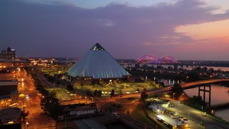 Hermosa-Noche-Toma-Aérea-De-La-Pirámide-De-Memphis-El-Puente-Hernando-De-Soto-Y-El-Paisaje-Urbano-Al-Atardecer-1