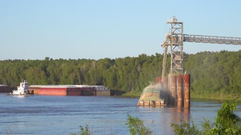 Workers-load-a-grain-barge-along-the-Mississippi-River-while-a-tugboat-arrives-nearby