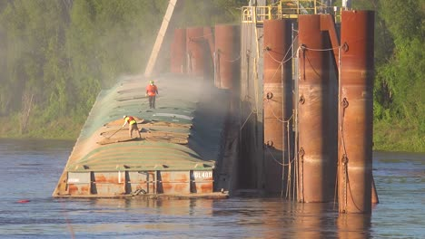 Workers-load-a-grain-barge-along-the-Mississippi-River-near-a-large-mill