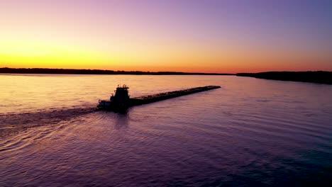 Muy-Buena-Antena-De-Un-Remolcador-Empujando-Una-Barcaza-Por-El-Río-Mississippi-Cerca-De-Memphis-Tennessee-Al-Atardecer-O-Al-Anochecer