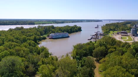 Aerial-shot-of-a-paddlewheel-steamboat-luxury-cruise-ship-docked-in-a-bay-on-the-Mississippi-River