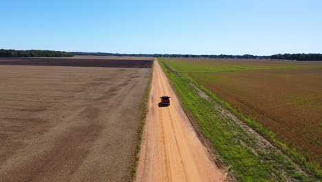 Aerial-shot-of-a-red-pickup-truck-traveling-on-a-dirt-road-in-a-rural-farm-area-of-Mississippi