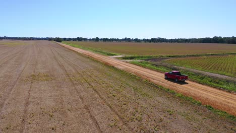 Aerial-shot-of-a-red-pickup-truck-traveling-on-a-dirt-road-in-a-rural-farm-area-of-Mississippi-1