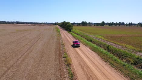 Aerial-shot-of-a-red-pickup-truck-traveling-on-a-dirt-road-in-a-rural-farm-area-of-Mississippi-2