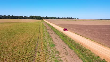 Aerial-shot-of-a-red-pickup-truck-traveling-on-a-dirt-road-in-a-rural-farm-area-of-Mississippi-3