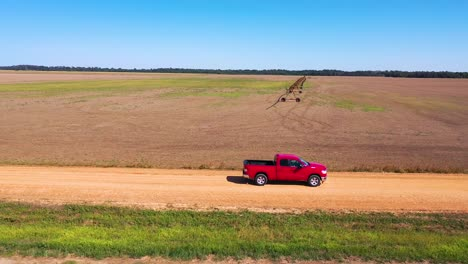Aerial-shot-of-a-red-pickup-truck-traveling-on-a-dirt-road-in-a-rural-farm-area-of-Mississippi-4