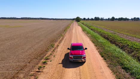 Aerial-shot-of-a-red-pickup-truck-traveling-on-a-dirt-road-in-a-rural-farm-area-of-Mississippi-6