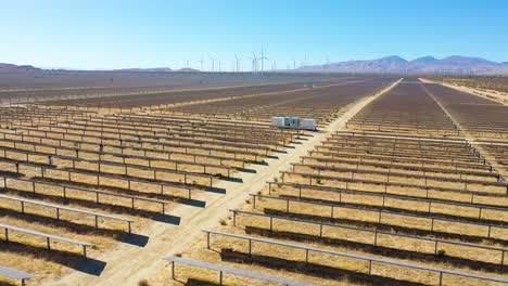 Aerial-over-a-solar-farm-reveals-a-wind-farm-in-the-distance-Mojave-Desert-California-suggests-clean-renewable-green-energy-sources