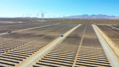 Aerial-over-a-solar-farm-reveals-a-wind-farm-in-the-distance-Mojave-Desert-California-suggests-clean-green-renewable-energy-sources