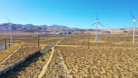 Drone-aerial-of-a-freight-train-traveling-through-vast-solar-and-wind-array-in-Mojave-desert-California-1