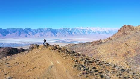 Antena-De-Drones-Como-Un-Hombre-Se-Encuentra-En-El-Borde-De-Una-Vasta-Vista-Abierta-Del-Desierto-Del-Valle-De-Owens-Y-El-Lecho-Del-Lago-Owens-En-Las-Sierras-Orientales-De-California