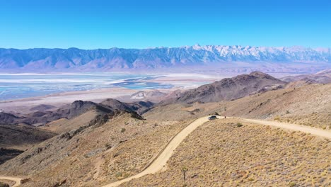 Aerial-of-a-4WD-wheel-drive-vehicle-on-a-dirt-road-through-the-Eastern-Sierras-with-Mt-Whitney-and-the-Owens-Valley-desert-and-dry-lake-bed-distant
