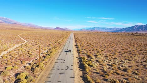 Aerial-of-a-4WD-wheel-drive-vehicle-on-a-paved-road-across-the-Owens-Valley-desert-region-suggests-remote-Eastern-Sierra-adventure-1