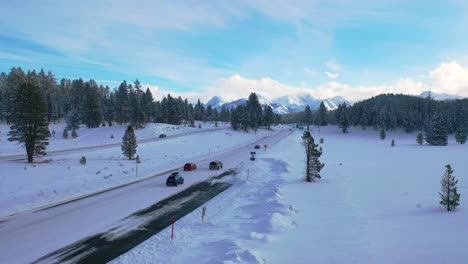 2020---aerial-of-cars-driving-travel-on-icy-snow-covered-mountain-road-in-the-Eastern-Sierra-Nevada-mountains-near-Mammoth-California