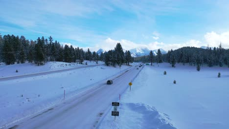 2020---aerial-of-cars-driving-travel-on-icy-snow-covered-mountain-road-in-the-Eastern-Sierra-Nevada-mountains-near-Mammoth-California-1