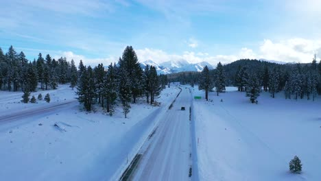 2020---aerial-of-cars-driving-slowly-on-icy-snow-covered-mountain-road-in-the-Eastern-Sierra-Nevada-mountains-near-Mammoth-California