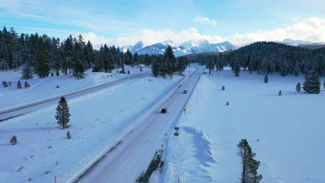 2020---aerial-of-cars-driving-slowly-on-icy-snow-covered-mountain-road-in-the-Eastern-Sierra-Nevada-mountains-near-Mammoth-California-1