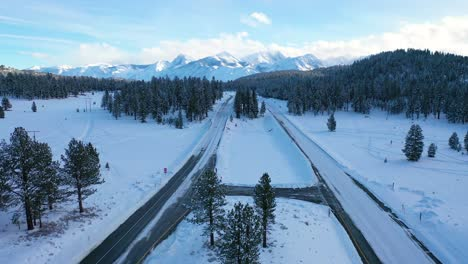 2020---aerial-of-cars-driving-slowly-on-icy-snow-covered-mountain-road-in-the-Eastern-Sierra-Nevada-mountains-near-Mammoth-California-2