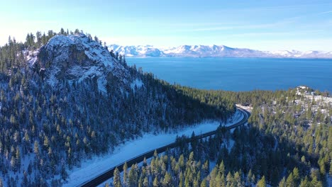 2020--beautiful-aerial-of-Highway-50-approaching-Lake-Tahoe-in-snow-and-winter-with-traffic-on-highway-below
