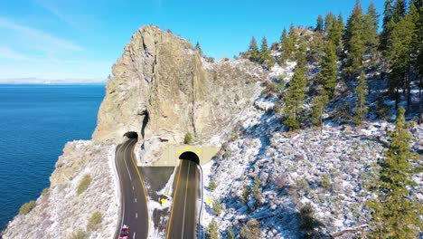 2020--winter-snow-aerial-Cave-Rock-tunnel-along-the-eastern-shore-of-Lake-Tahoe-Nevada-with-road-and-traffic-below