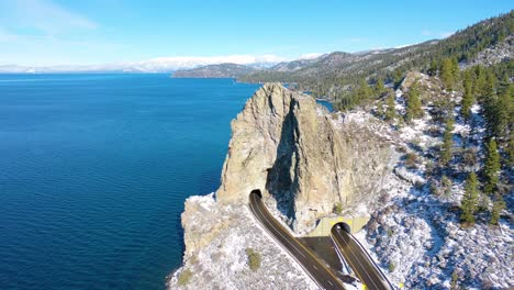 2020--winter-snow-aerial-Cave-Rock-tunnel-along-the-eastern-shore-of-Lake-Tahoe-Nevada-with-road-and-traffic-below-1