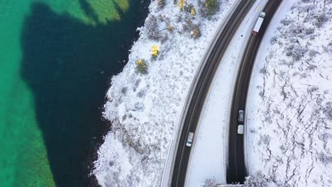 2020---top-down-aerial-POV-of-a-car-traveling-on-a-snowy-road-through-a-tunnel-beside-a-lake