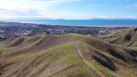 2020---aerial-over-the-pacific-coastal-green-hills-and-mountains-behind-Ventura-California-including-suburban-homes-and-neighborhoods
