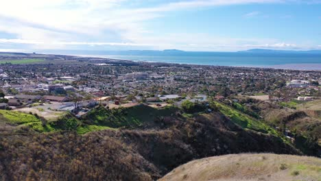 2020---aerial-over-the-pacific-coastal-green-hills-and-mountains-behind-Ventura-California-including-suburban-homes-and-neighborhoods-1