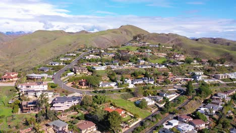 2020---aerial-over-the-pacific-coastal-green-hills-and-mountains-behind-Ventura-California-including-suburban-homes-and-neighborhoods-2