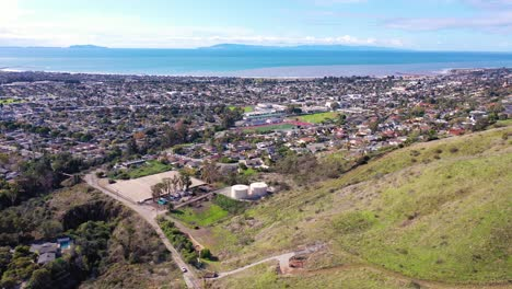 2020---aerial-over-the-pacific-coastal-green-hills-and-mountains-behind-Ventura-California-including-suburban-homes-and-neighborhoods-3