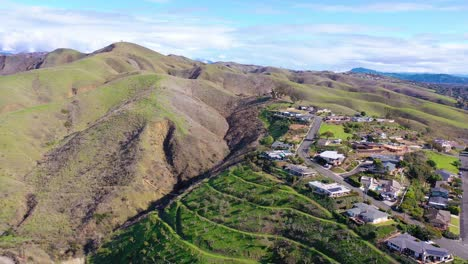 2020---aerial-over-the-pacific-coastal-green-hills-and-mountains-behind-Ventura-California-including-suburban-homes-and-neighborhoods-4