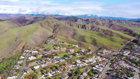 2020---aerial-over-the-pacific-coastal-green-hills-and-mountains-behind-Ventura-California-including-suburban-homes-and-neighborhoods-5