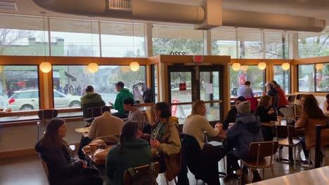 La-Fuerte-Nieve-Del-Invierno-Cae-Afuera-Mientras-La-Gente-Se-Sienta-En-El-Interior-De-Una-Cafetería-O-Restaurante-En-Portland-Oregón