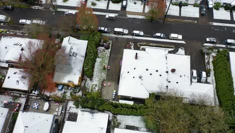 Top-down-aerial-over-snowy-winter-neighborhood-houses-suburbs-in-snow-in-Portland-Oregon