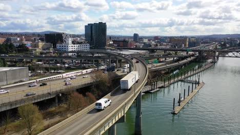 High-angle-aerial-shot-of-freeway-traffic-Amtrak-train-and-Willamette-River-in-Portland-Oregon