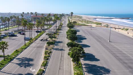 2020---aerial-of-surfers-crossing-abandoned-roads-beaches-of-Ventura-southern-california-during-covid-19-coronavirus-epidemic-as-people-stay-home-en-masse