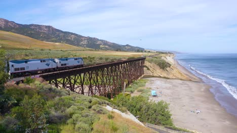 Aerial-shot-of-an-Amtrak-passenger-train-traveling-south-along-the-coast-of-Central-California-and-over-the-Gaviota-trestle