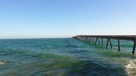 Aerial-over-a-long-oil-pier-extending-to-a-small-island-off-the-shore-of-Mussel-Shoals-Rincon-Beach-Santa-Barbara-California