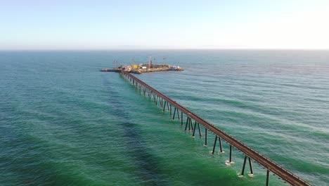 Vista-Aérea-over-a-long-oil-pier-extending-to-a-small-island-off-the-shore-of-Mussel-Shoals-Rincon-Beach-Santa-Barbara-California-1