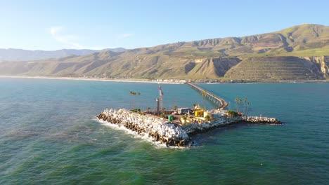 Aerial-over-a-long-oil-pier-extending-to-a-small-island-off-the-shore-of-Mussel-Shoals-Rincon-Beach-Santa-Barbara-California-3
