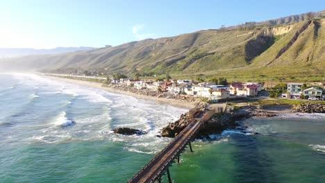 Aerial-over-a-long-oil-pier-and-beach-homes-the-shore-of-Mussel-Shoals-Rincon-Beach-Santa-Barbara-California