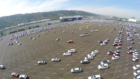 An-aerial-over-vast-mostly-empty-parking-lots-at-a-shipping-container-port-importing-cars