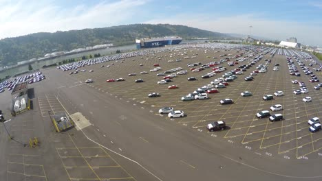 An-aerial-over-vast-mostly-empty-parking-lots-at-a-shipping-container-port-importing-cars-1