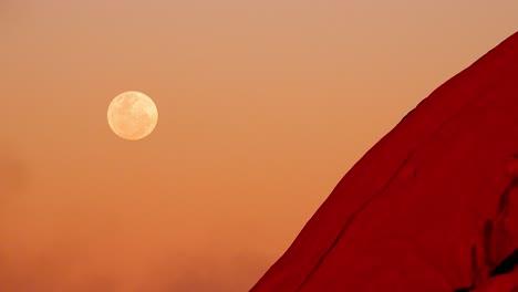 Beautiful-shot-of-the-full-moon-rising-next-to-Ayers-Rock-Uluru-Australia