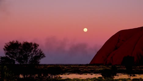 Beautiful-shot-of-the-full-moon-rising-next-to-Ayers-Rock-Uluru-Australia-during-a-dust-storm